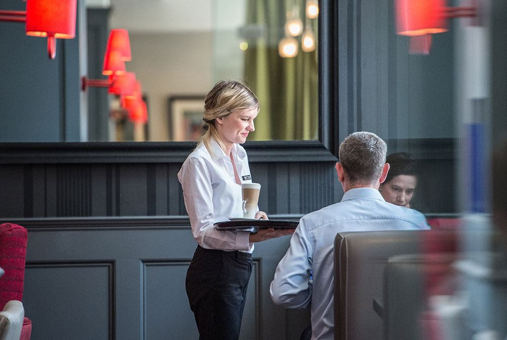 Waitress bringing coffee over to guests