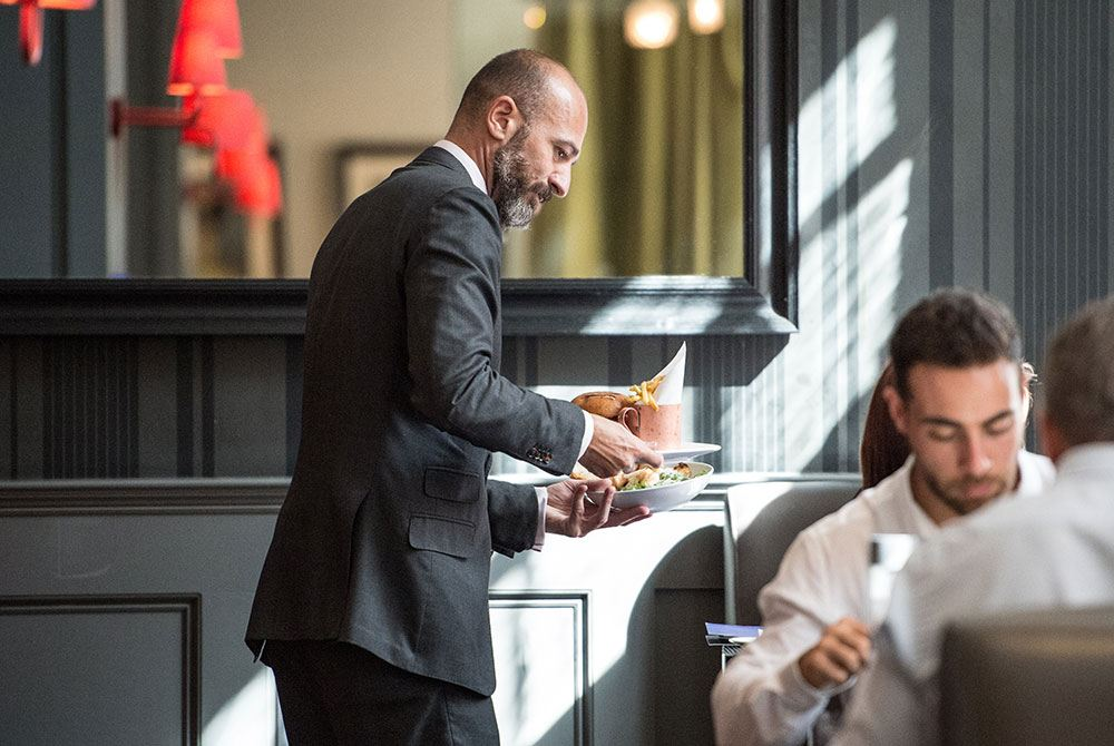 Waiter bringing out tasty dishes to hotel guests