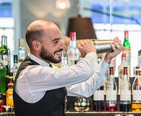 Smiling barman shaking a cocktail blender