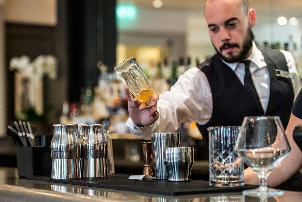 A bartender pouring smooth drinks from behind the bar